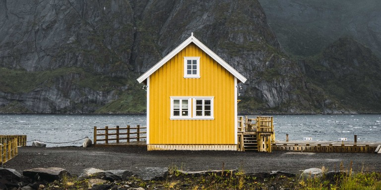Norway, Lofoten, remote yellow house at rocky coast