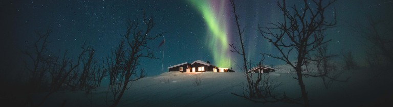 Beautiful Northern lights in the night sky above a lone cabin in Riksgransen, Sweden.