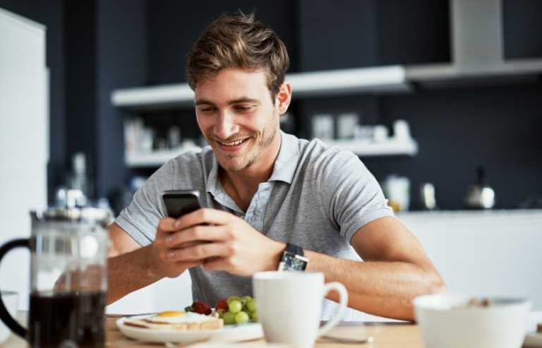 Shot of a happy young man using his cellphone while enjoying breakfast at home