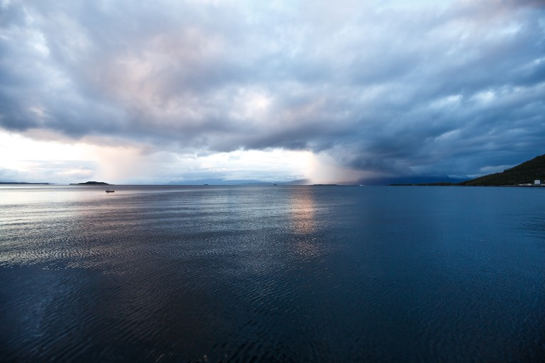Landscape with sea and clouds in the midnight of polar day in Harstad, Norway.