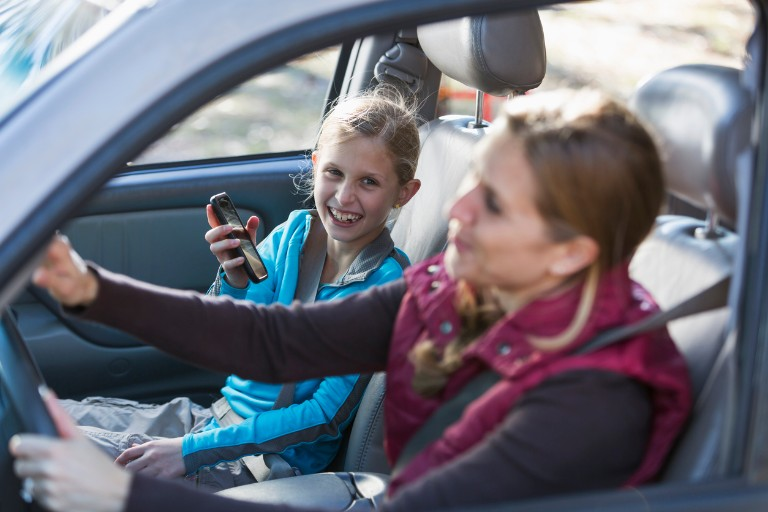 A happy mother and daughter on a road trip, travelling in a car.  The focus is on the little girl, 9 years hold, sitting in the front passenger seat, smiling at her mom, showing her something on her mobile phone.