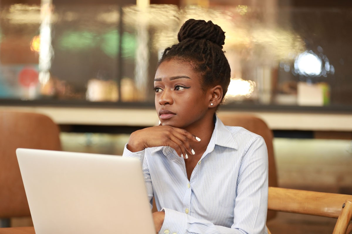 Young black girl sitting with laptop at table and looking away dreamily.